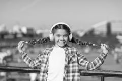 Girl child listen music outdoors with modern headphones. Listen for free. Get music family subscription. Access to royalty free stock photos
