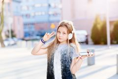 Girl child listen to the music from her smartphone Stock Images