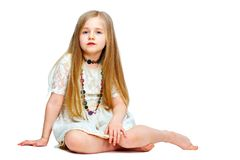 Girl child with long blond hair siting on a floor.fashion portr. Ait isolated on white background Royalty Free Stock Photos