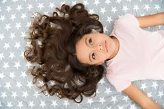 Girl child with long curly hair lay on bed top view. Child perfect curly hairstyle looks cute. Conditioner mask organic. Oil keep hair shiny and healthy Royalty Free Stock Photography