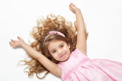 Girl child with long hair lie on white and open arms, dressed in pink Royalty Free Stock Images