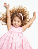 Girl child with long hair lie on white and open arms, dressed in pink Stock Images