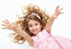 Girl child with long hair lie on white and open arms, dressed in pink Royalty Free Stock Image