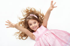 Girl child with long hair lie on white and open arms, dressed in pink Stock Photos