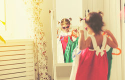Girl child looks into the mirror and choose dresses Stock Images