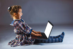 Girl child looks rejoices computer Royalty Free Stock Images