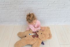 girl, child measures the temperature of a toy bear, against a white brick wall stock image