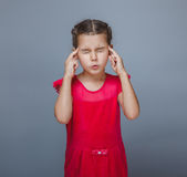 Girl child migraine headache on a gray background Stock Photos