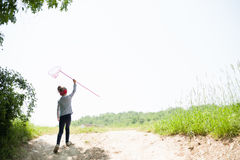 Girl, child, net, lifestyle, summer, forest, insects, joy, environment, nature. Girl with a butterfly net out of the woods into the meadow royalty free stock photography