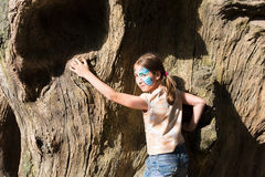 Girl child outdoors climb tree with butterfly face painting Royalty Free Stock Image