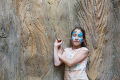 Girl child outdoors near tree with butterfly face painting. Small girl portrait with funny face art painting. Female child near big old tree with blue butterfly stock photo