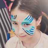 Girl child outdoors in tree with butterfly face painting royalty free stock photography