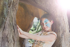 Girl child outdoors in tree with butterfly face painting Royalty Free Stock Photos