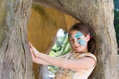 Girl child outdoors in tree with butterfly face painting Royalty Free Stock Images