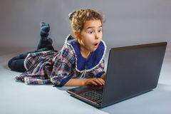 The girl child is playing in a laptop surprised on Royalty Free Stock Image