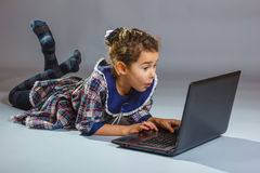 The girl child is playing in a notebook on gray Royalty Free Stock Image