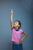 Girl child pointing at the sky on a gray Stock Photos