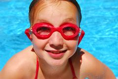 Girl child pool. Portrait of a smiling girl in red goggles Stock Photo