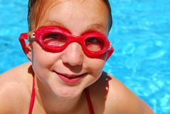 Girl child pool. Portrait of a smiling girl in red goggles Stock Photography