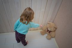 Girl, child punishes, puts in the corner of the toy bear. Punishes, puts in the corner of the toy bear girl, child Stock Images