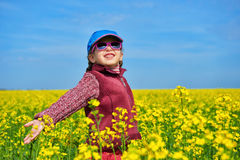 Girl child in rapeseed field with bright yellow flowers, spring landscape Stock Images