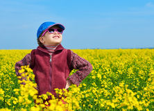 Girl child in rapeseed field with bright yellow flowers, spring landscape Stock Photos
