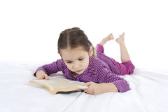 Girl child reading book lying on bed Royalty Free Stock Images