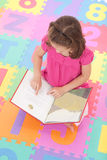 Girl child reading kids book. Young girl reading book on colorful floor mat Royalty Free Stock Images