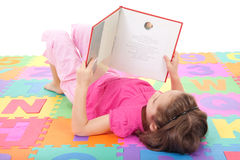 Girl child reading kids book on alphabet. Girl reading book on alphabet letters floor mat. Isolated on white Royalty Free Stock Image