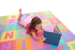 Girl child reading kids book on alphabet mat. Girl reading book on colorful alphabet floor mat. Isolated on white Stock Images