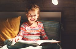 Girl child reads book in bed. Before bedtime Stock Photo