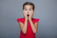 Girl child in red dress suffers surprise on gray Royalty Free Stock Images