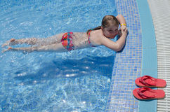Girl child relaxing in tropical pool Royalty Free Stock Photos