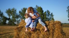 A girl with a child resting on a haystack stock video