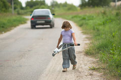 Girl child riding  scooter near car on  road In  countryside, ch Stock Photography