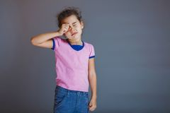 Girl child rubs his eyes on a gray background Royalty Free Stock Image