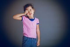 Girl child rubs his eyes on a gray background Stock Photos