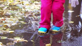 Girl child runs through puddles stock footage