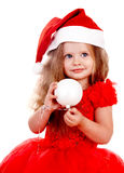 Girl child in santa hat with christmas ball. Royalty Free Stock Photo