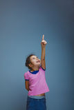 Girl child shows finger up on a gray background Stock Images