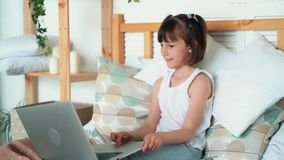 Girl child sits on bed, uses laptop, plays computer game, slow motion. Girl child sits on bed, uses laptop and plays computer game, enjoys something, slow motion stock video