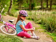 Girl child sitting near bicycle. Stock Photography
