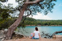 Mother and daughter sitting under a tree on the beach against th. Girl and child sitting on a pebble next to a spruce tree h background of blue sea and green stock photography