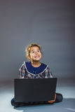 Girl child sitting playing laptop surprised on a Royalty Free Stock Photo