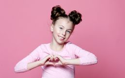 Girl child smiling in love showing heart symbol and shape with hands. Emotion, childhood and people concept: beautiful girl child over pink background smiling stock photography