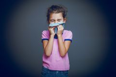 Girl child sneezes into handkerchief on a gray. Girl child sneezes into a handkerchief on gray background Stock Photography