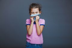 Girl child sneezes into  handkerchief on a gray. Girl child sneezes into a handkerchief on gray background Stock Images