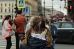 girl child stands with his back to crosswalk Stock Photo