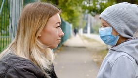 A girl with a child stands on the road in a protective medical mask. Dense smog on the streets. Epidemic of the flu stock video