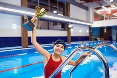 Girl child with swimmer Champion cup in hand the pool Royalty Free Stock Photos
